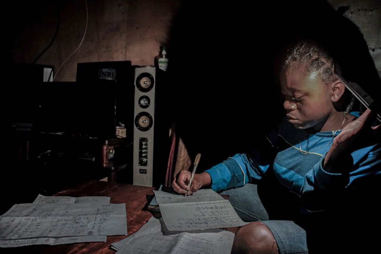 Goma, Democratic Republic of Congo, April 27-28 2020. With schools closed during Congo's period of confinement, and the city implementing regular power cuts, my 13-year-old sister Marie studies at home by the light of a mobile phone. © Arlette Bashizi for Fondation Carmignac
