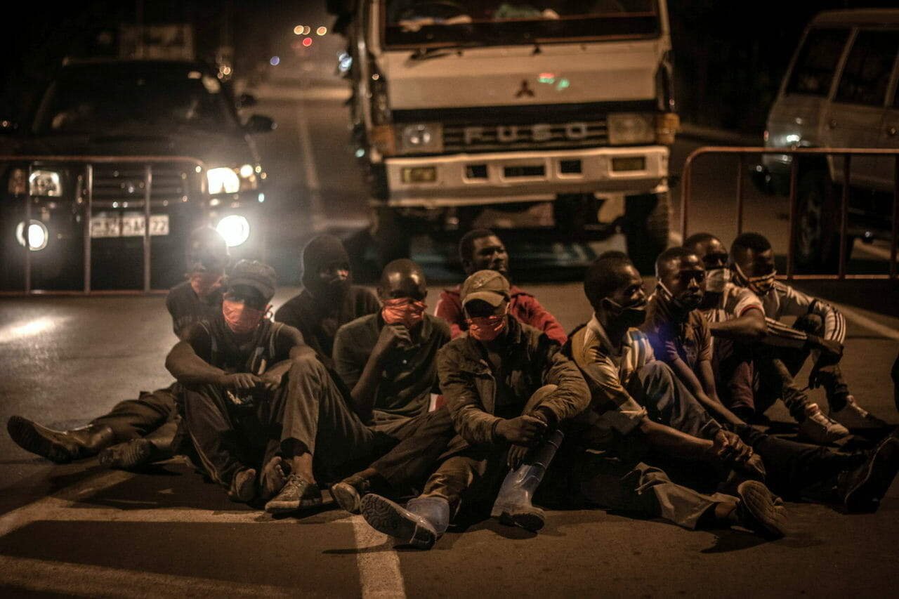 Goma, DRC, May 20th, 2020. Men sit on a road after being detained by police for breaking a new curfew imposed to limit the spread of coronavirus in the eastern Congolese city of Goma on Wednesday. © Guerchom Ndebo for Fondation Carmignac