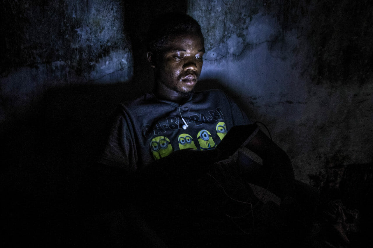 Mbudi, Kinshasa, DRC, May 2020. After paying to charge his phone at a communal charging station powered by a generator, a youth named David reads from his screen in the darkness in Mbudi, Kinshasa. © Justin Makangara for Fondation Carmignac