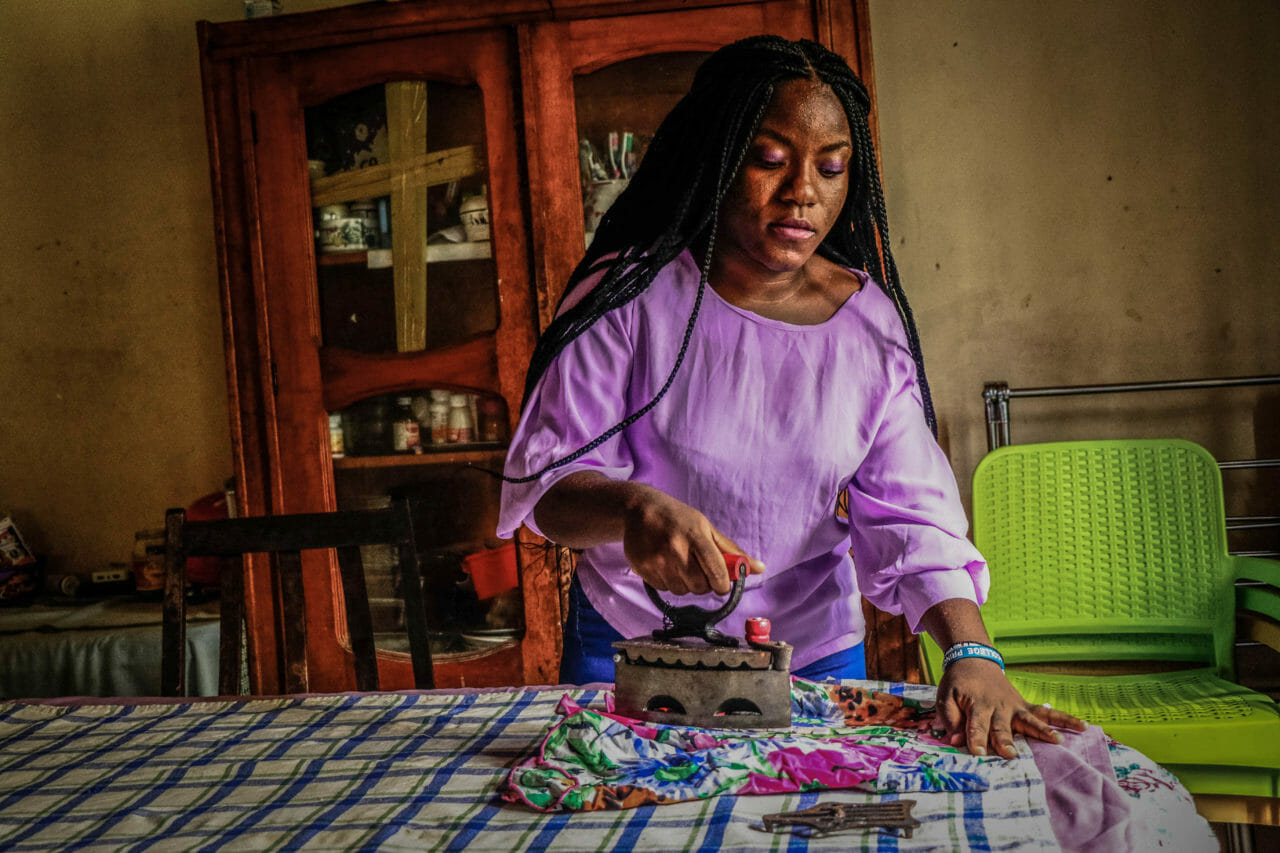 Kinshasa, DRC, May 2020. A woman named Laeticia uses a coal-heated iron to press clothing due to a lack of electricity in Kinshasa this month. © Justin Makangara for Fondation Carmignac