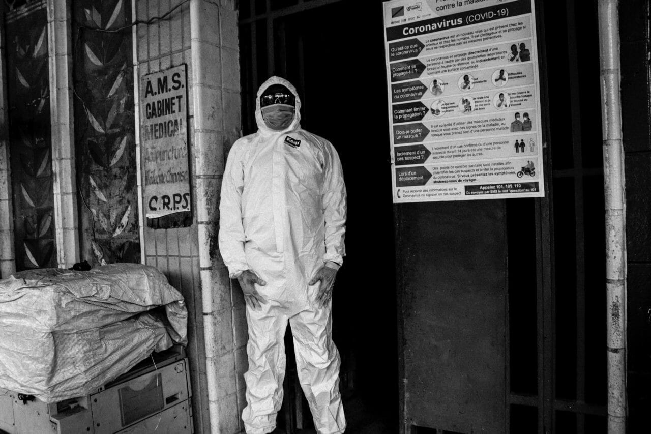 Kinshasa, Democratic Republic of Congo, mid-March, 2020. A member of the COVID-19 response team wears protective equipment at the entrance to a building in the Gombe commune of DR Congo's Capital. The responders were at the main entrance of the building to raise awareness among apartment residents about social distancing and to take the temperature of anyone entering or leaving the building, where there are around 75 families and offices.  © Justin Makangara for Fondation Carmignac